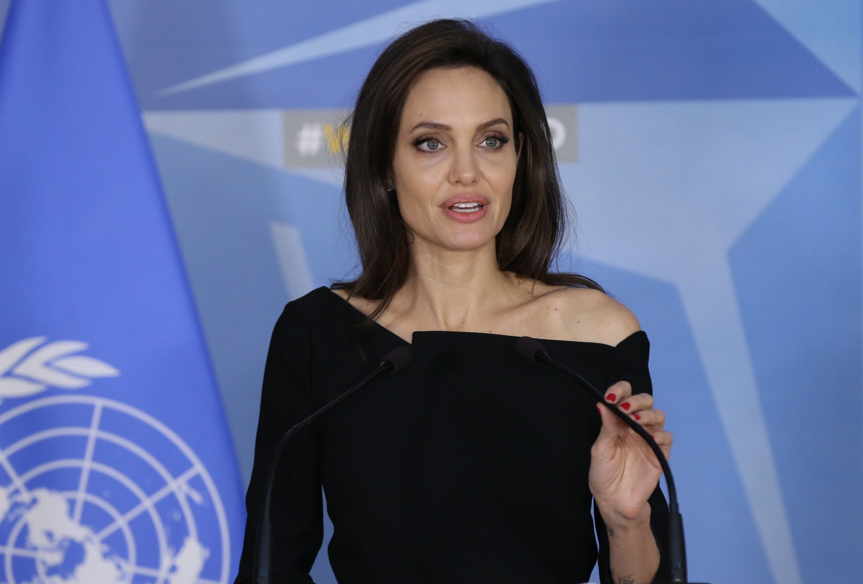 Angelina stands in front of a microphone