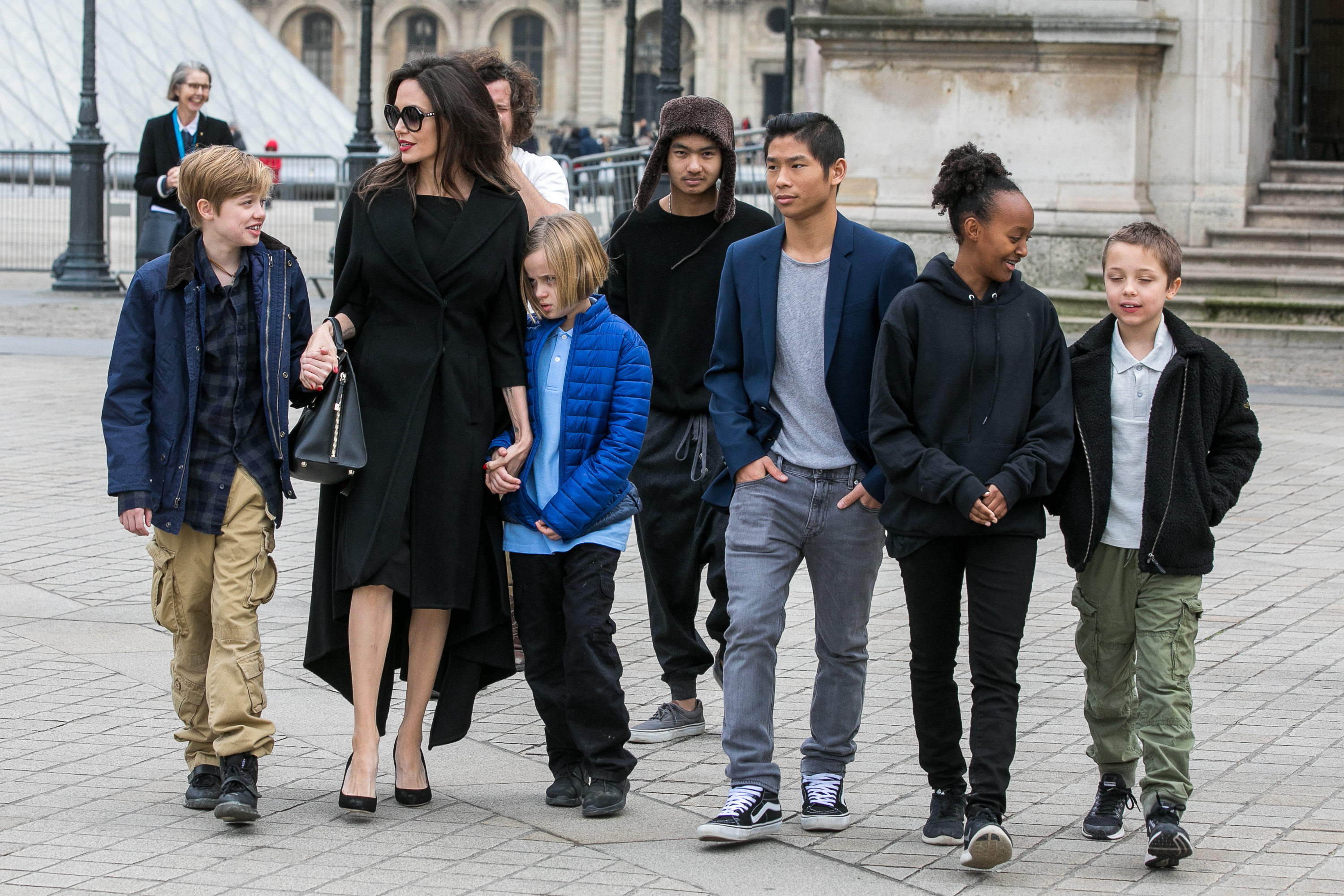 Angelina walking outdoors with her six children
