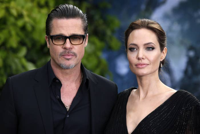 Brad in glasses with Angelina, both looking serious