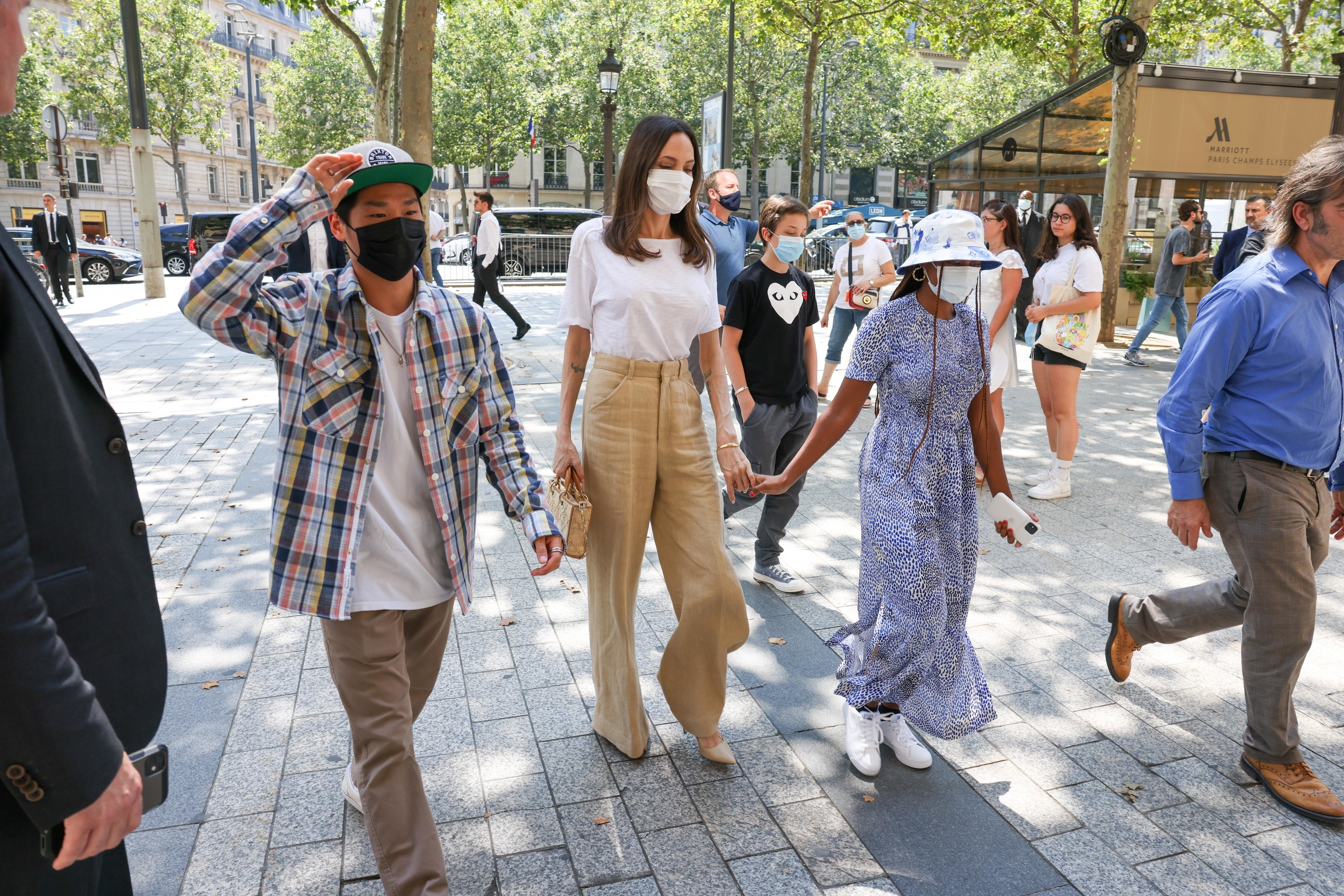 Angelina wearing a mask and holding hands with two of her children, also masked