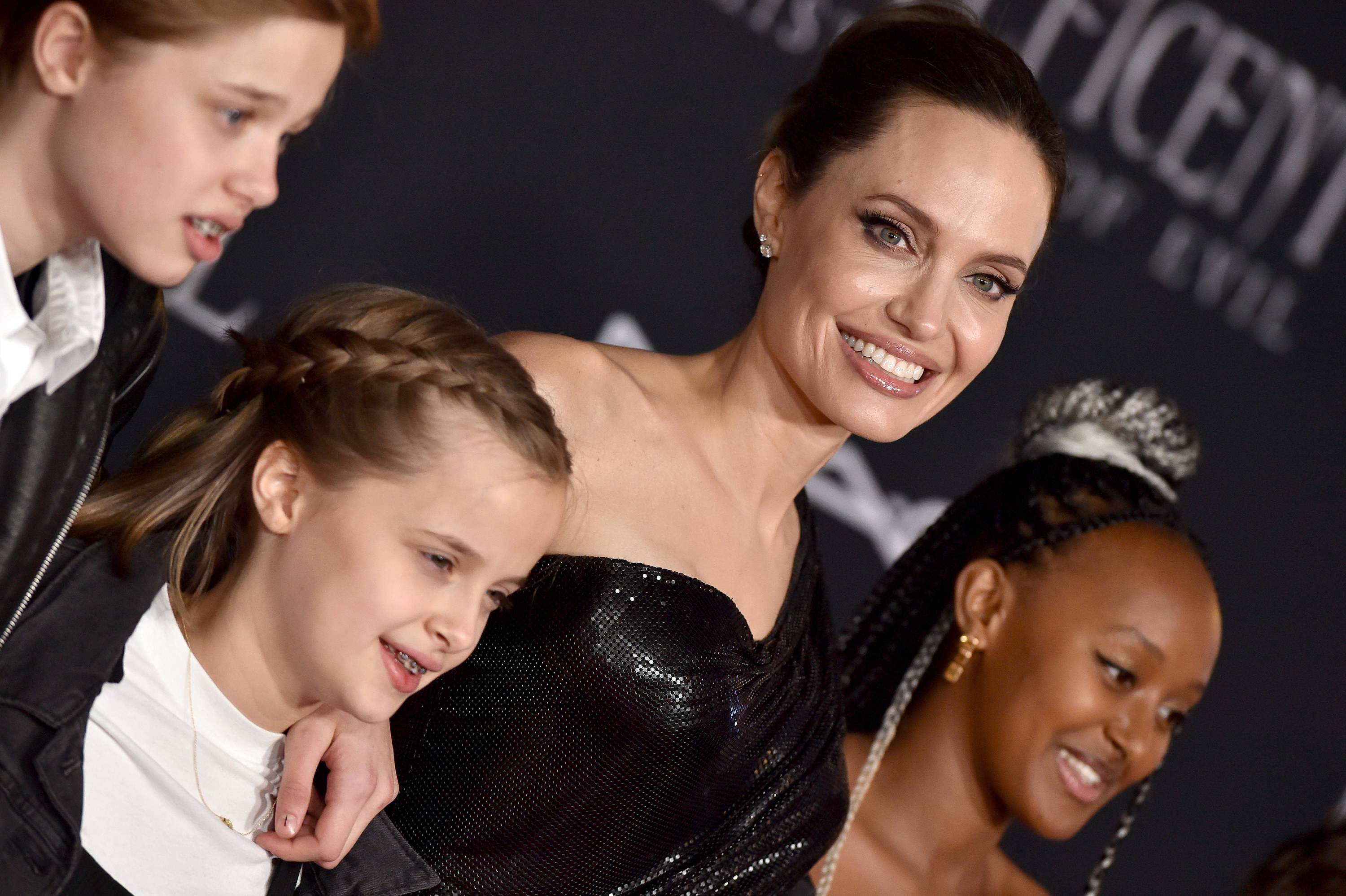 A smiling Angelina on the red carpet with three of her children