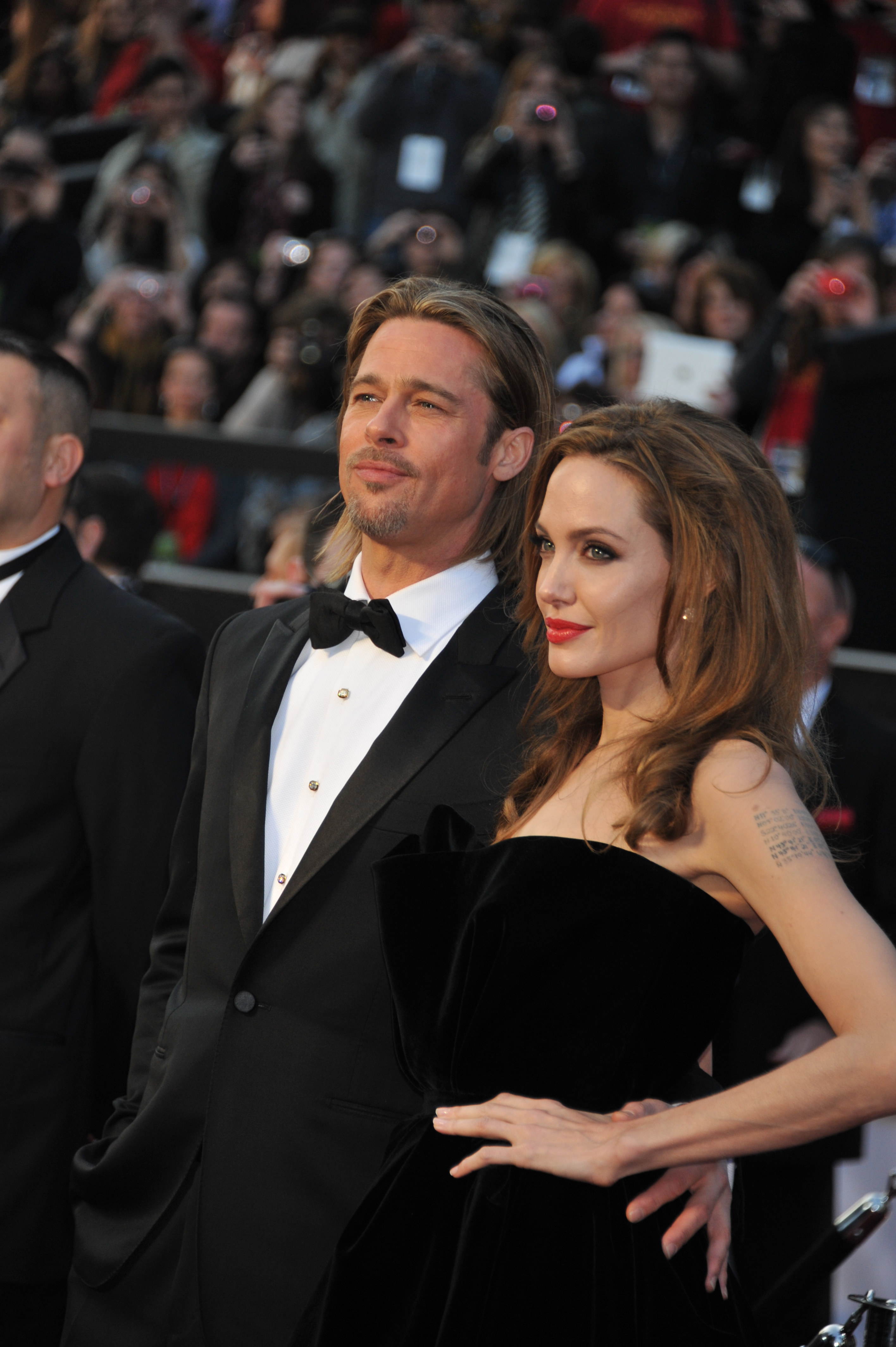 Brad and Angelina, both in formal attire, pose for photographers