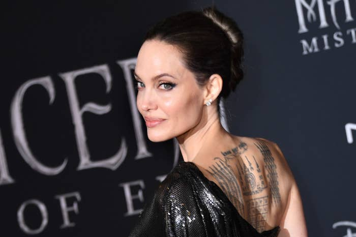 Angelina on the red carpet showing a back tattoo