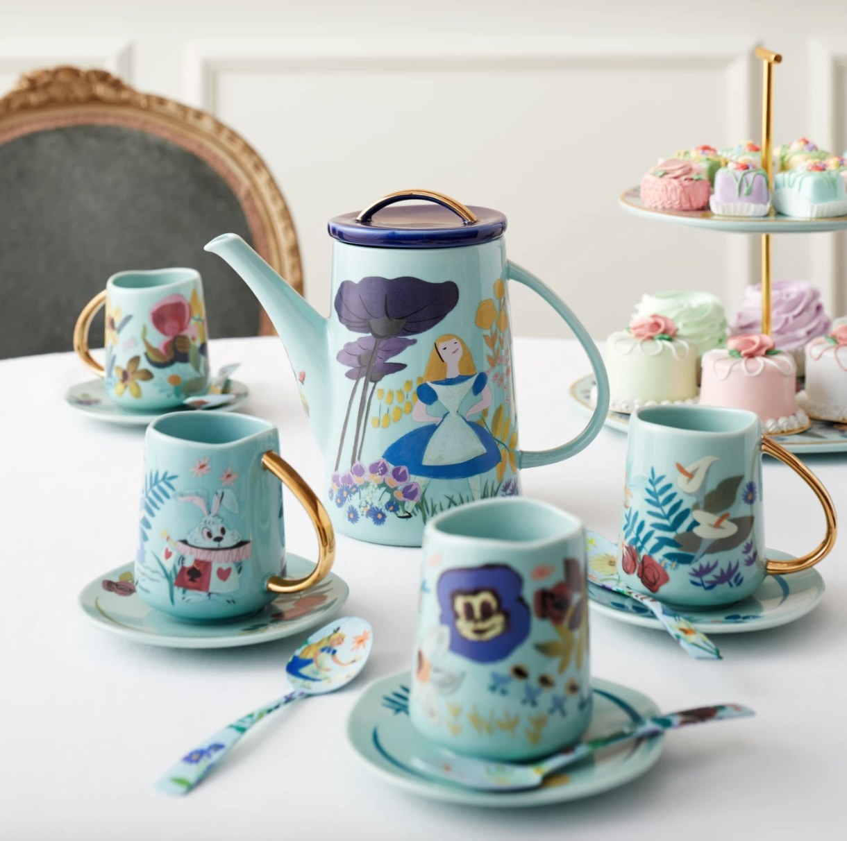 Four blue teacups and saucers with gold handles and Alice in Wonderland decoration
