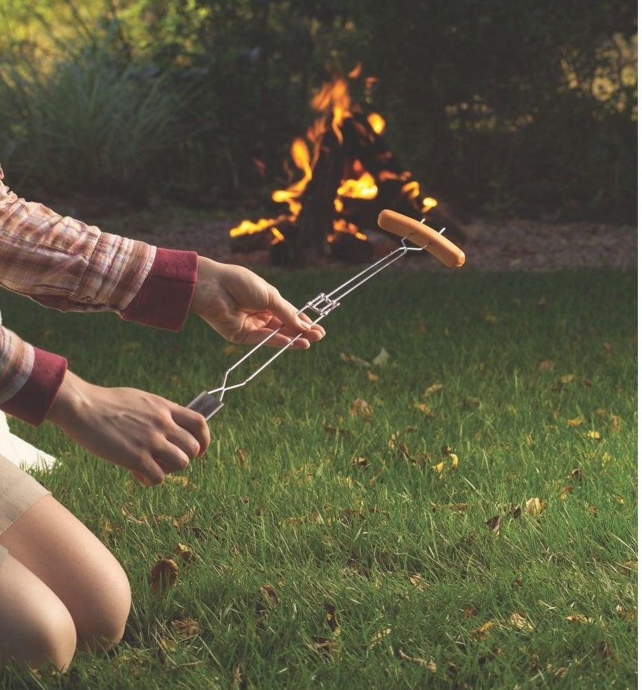 a hotdog wiener roasting on a rotisserie fork