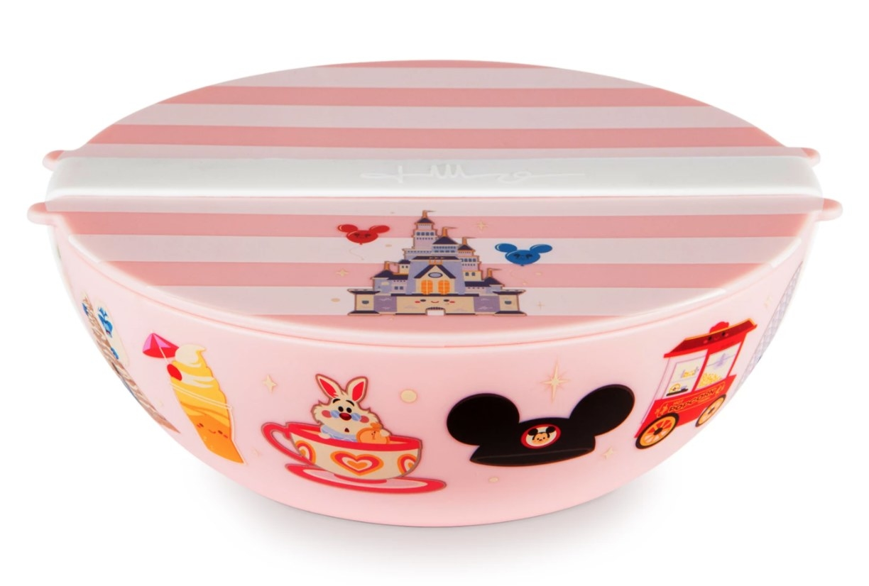 A pink travel bowl with lid and silicone strap with icons of Disney parks