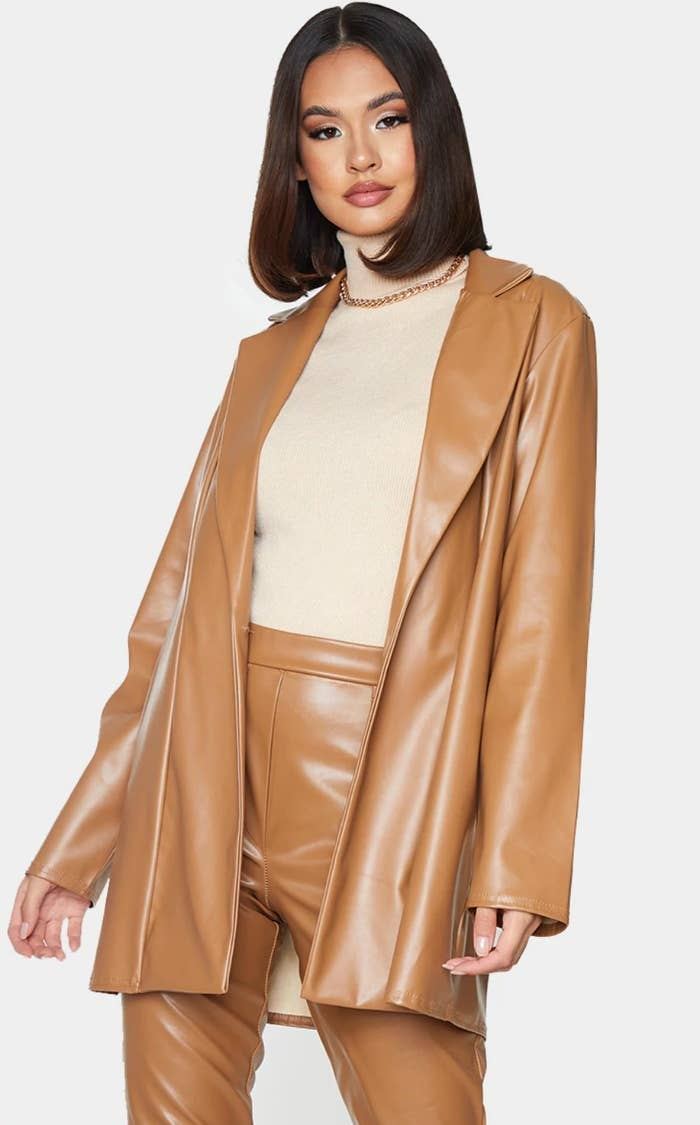 model wearing tan jacket over a cream turtle neck, chain link necklace, and matching faux leather pants