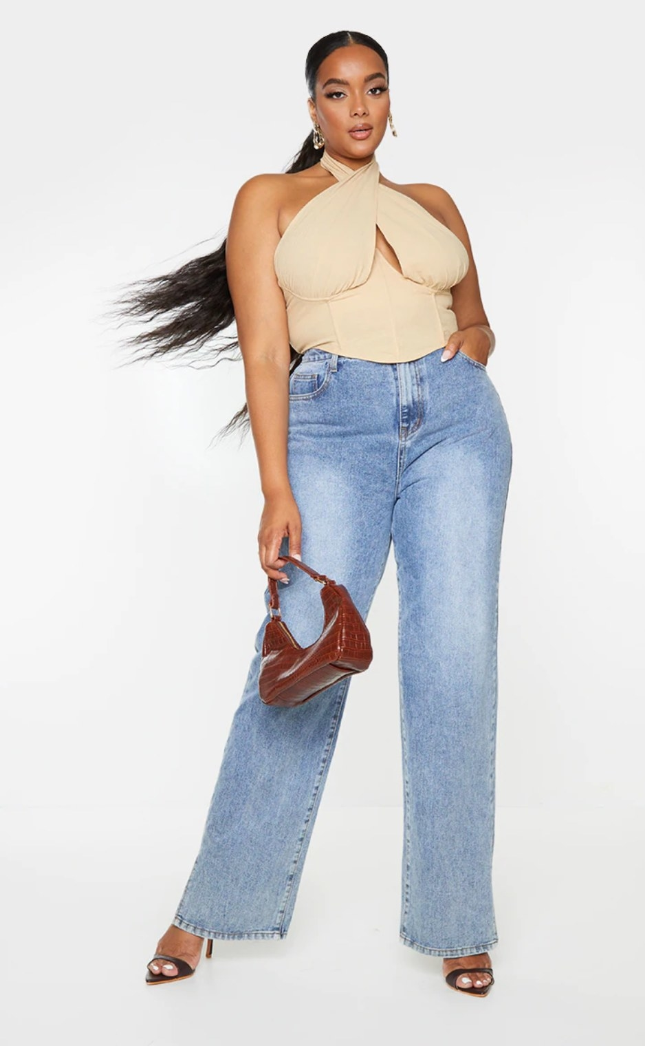 model wearing the oatmeal colored top with corset front tied at the neck over blue flare jeans with a brown handbag