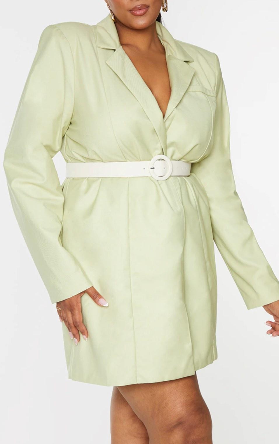 model wearing the white circle belt over a light green blazer dress