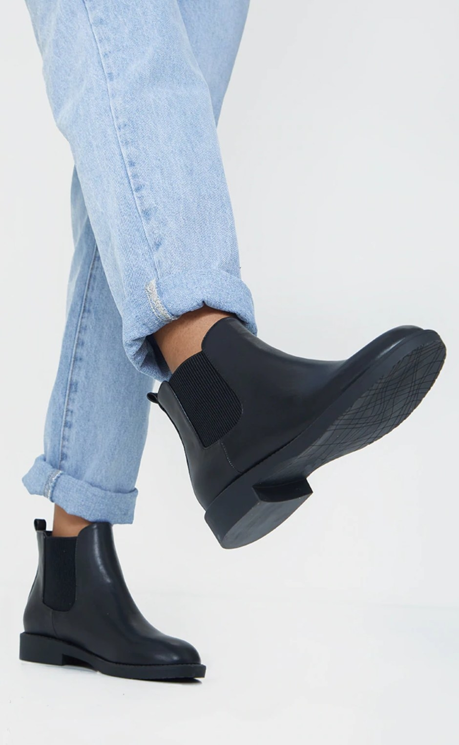 model wearing the black ankle boots with cuffed blue jeans