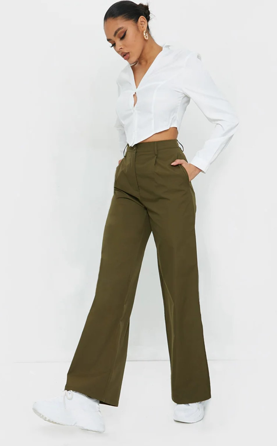 model wearing the green pants with white sneakers and a white top