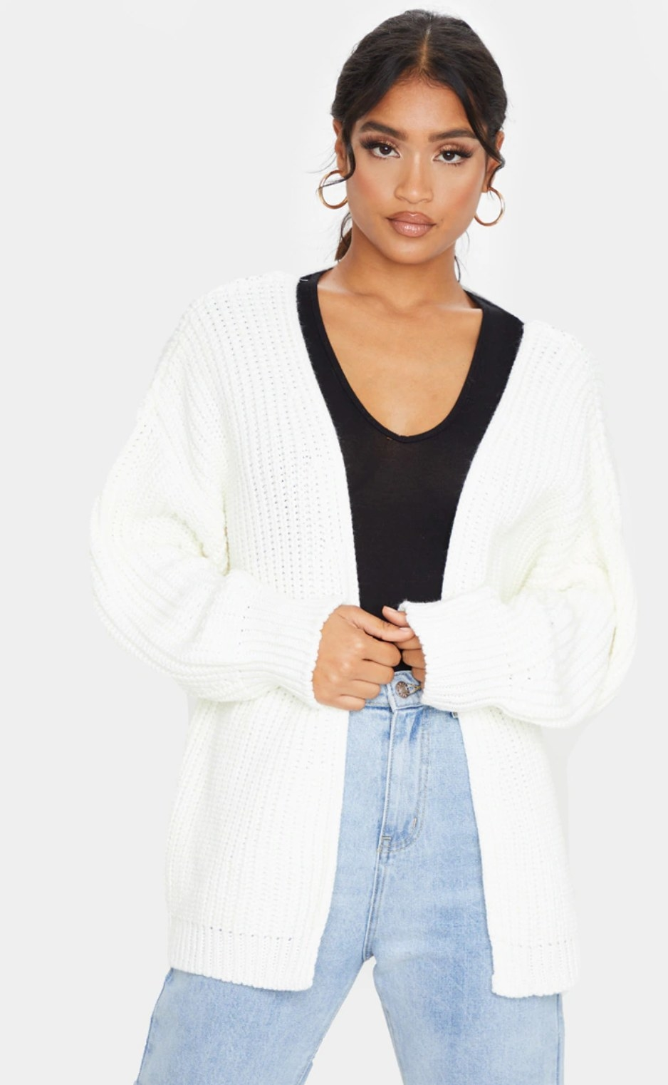 model wearing the white slouchy cardigan over a black top and blue jeans