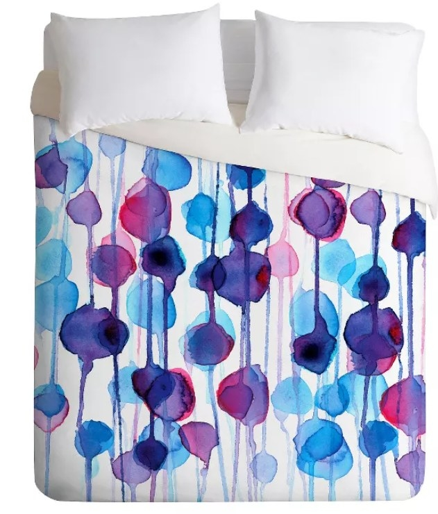 A duvet cover with abstract blue, red, and purple watercolors