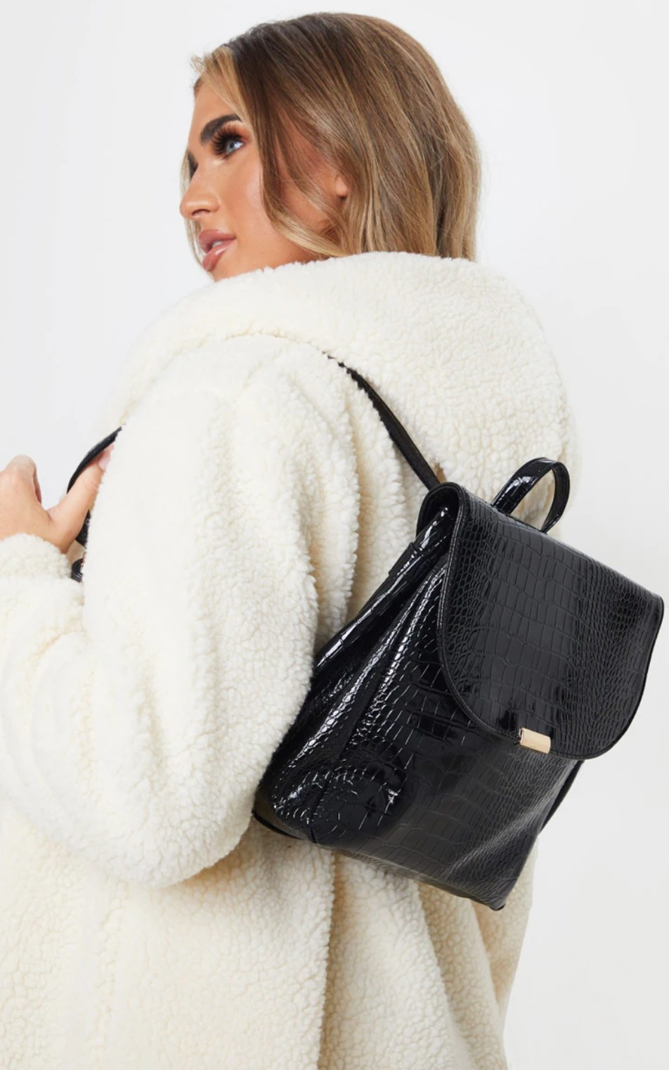 model wearing a fluffy white coat carrying the black backpack over one shoulder