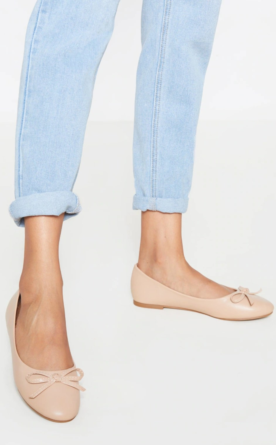 model wearing the nude ballet flats with a bow detail and blue jeans