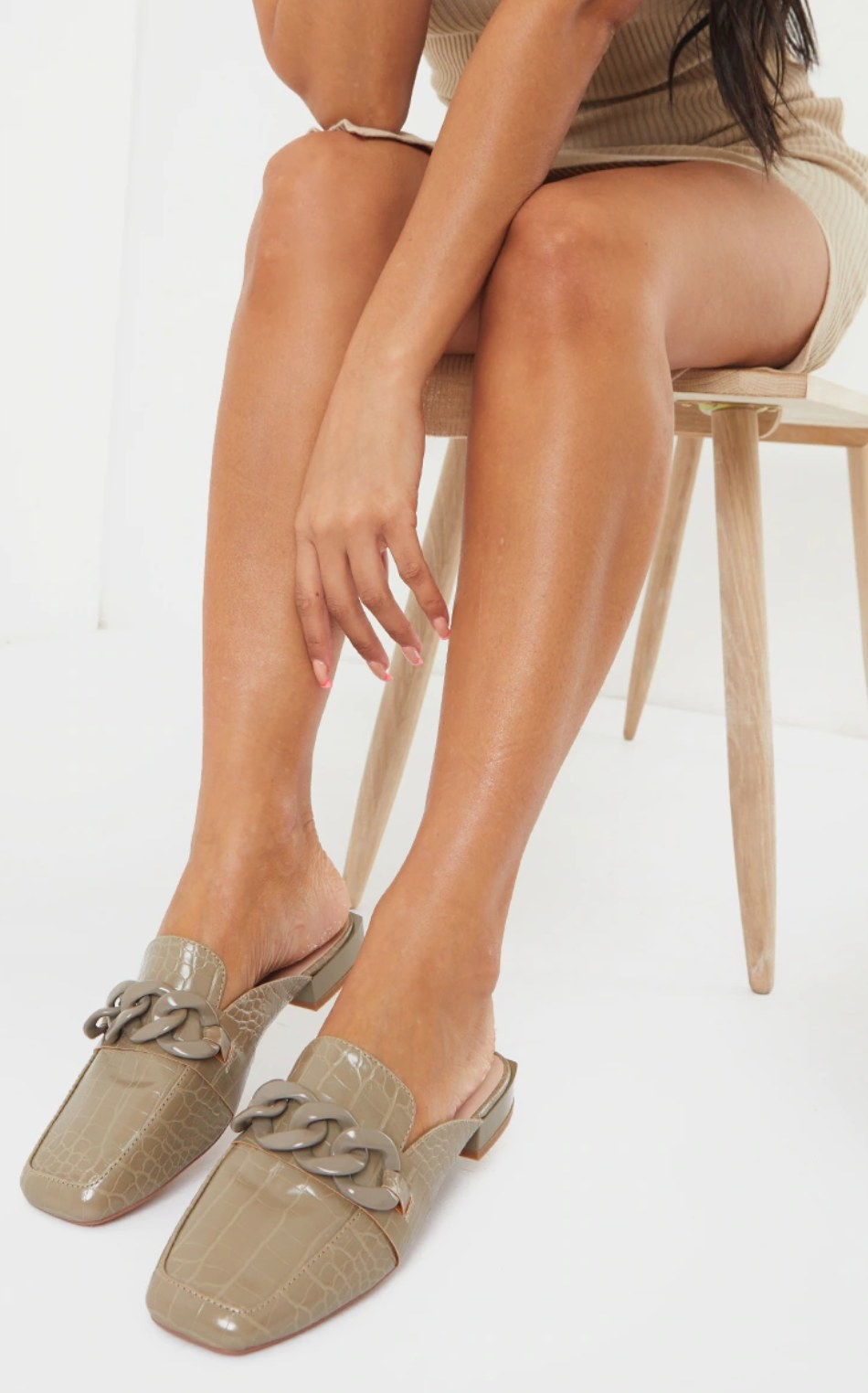 model sitting in a chair wearing the chain mules in taupe