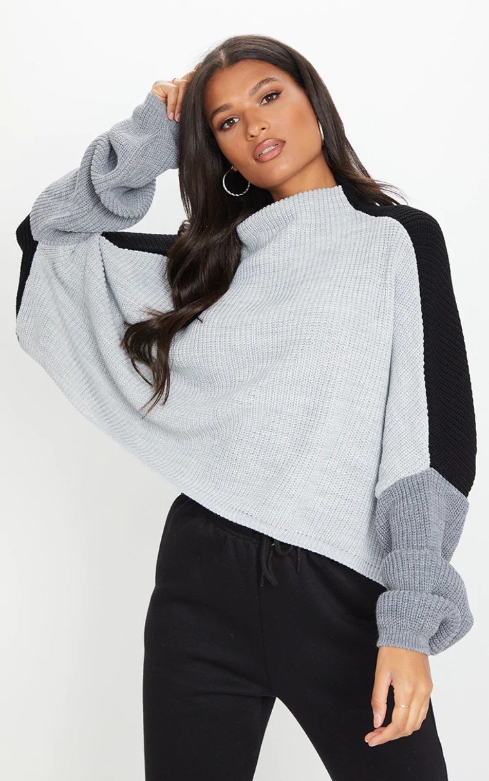 model wearing the sweater in heather gray with dark gray and black sleeves over black pants