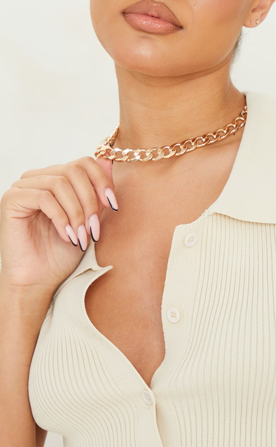 model wearing the necklace and holding it out from neck with one hand