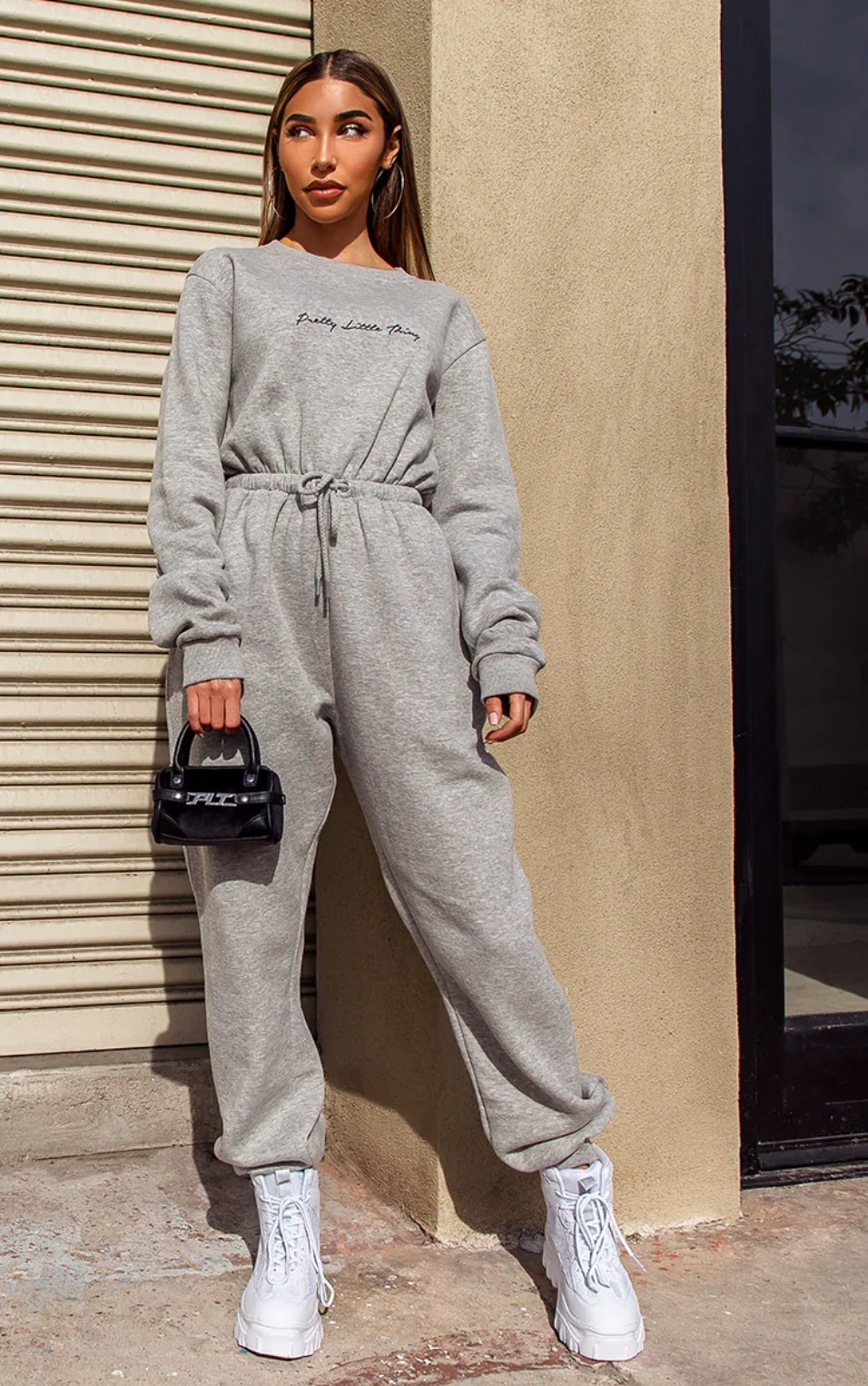 model wearing the gray sweatsuit with white boots and a small black handbag