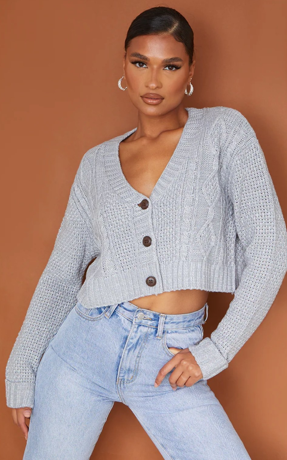 model wearing the gray cropped cardigan with blue jeans