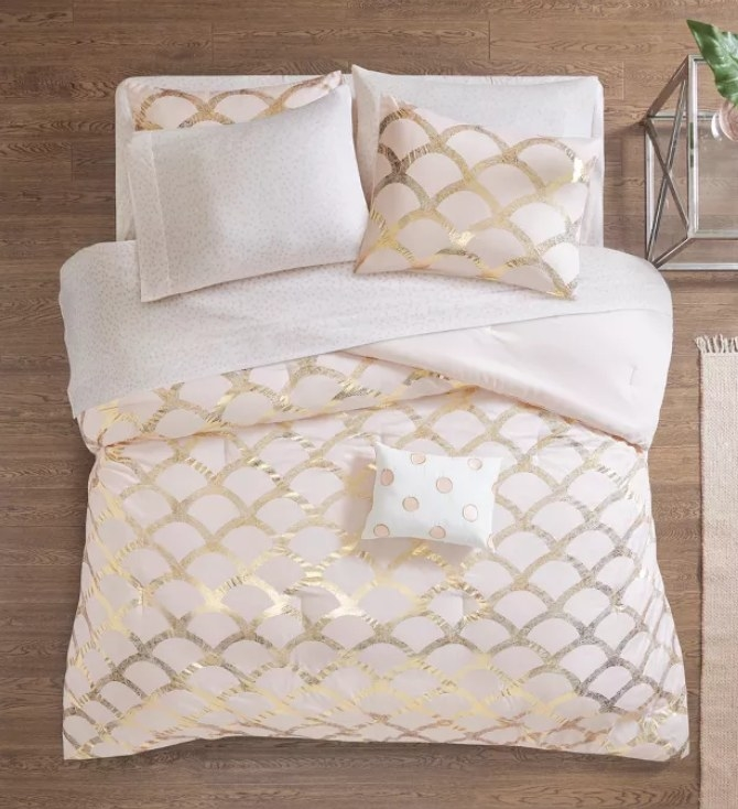 A pink metallic scallop print comforter on a bed