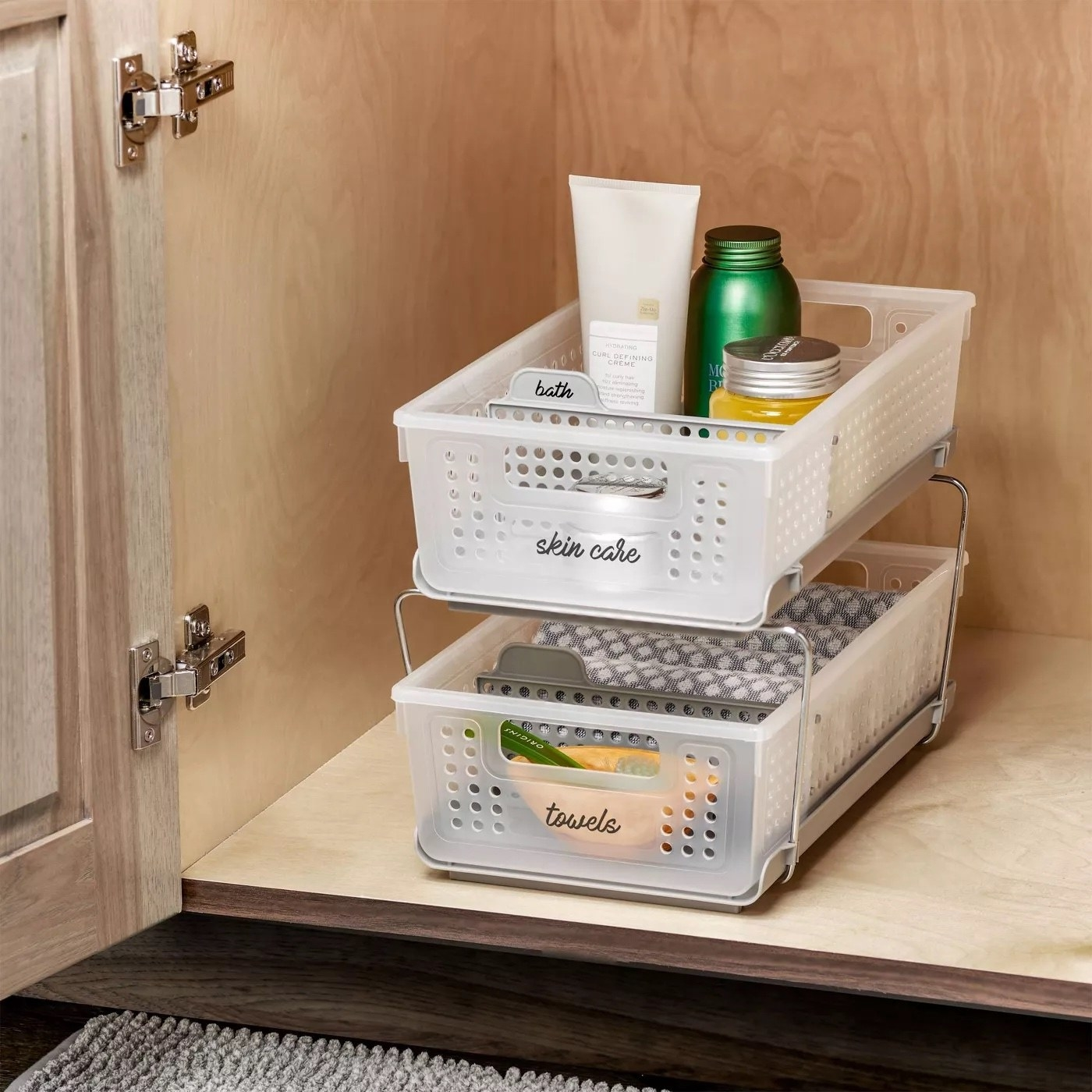 The two-tier organizer placed in a cabinet with assorted items inside