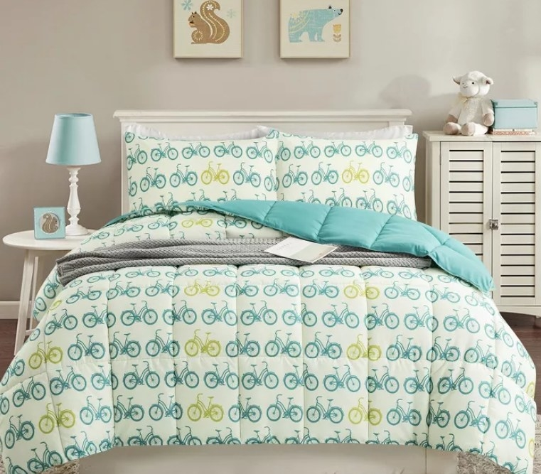 A comforter with bicycles all over it in different shades of green