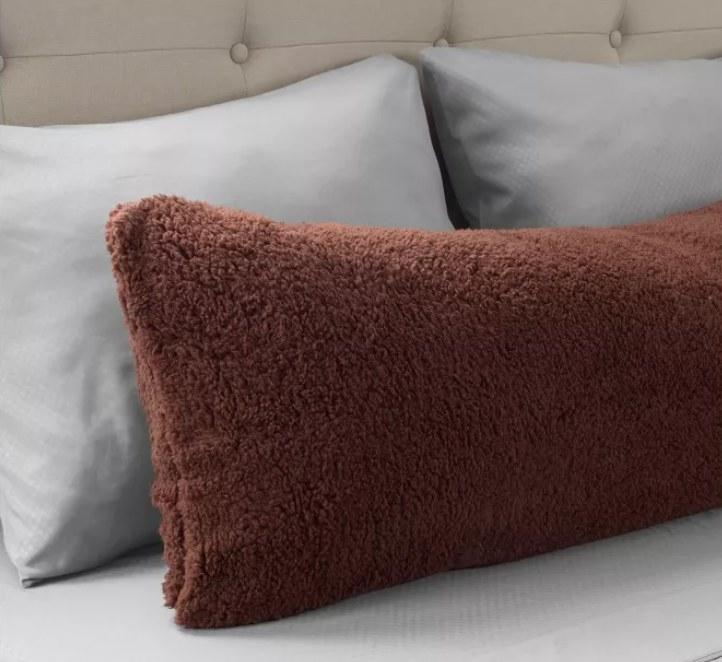 A brown fuzzy body pillow
