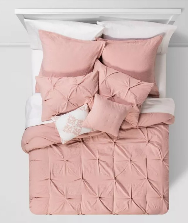 A pink comforter and set with pinched square patterns