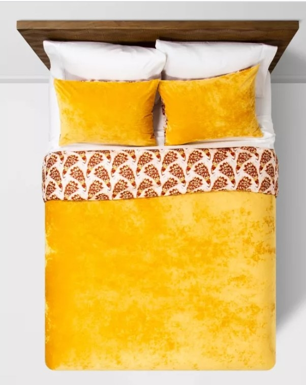 An amber velvet duvet with a folded over piece with a peacock print