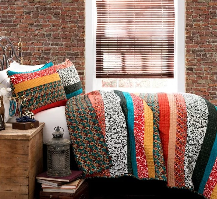 A mixed print quilt on a bed