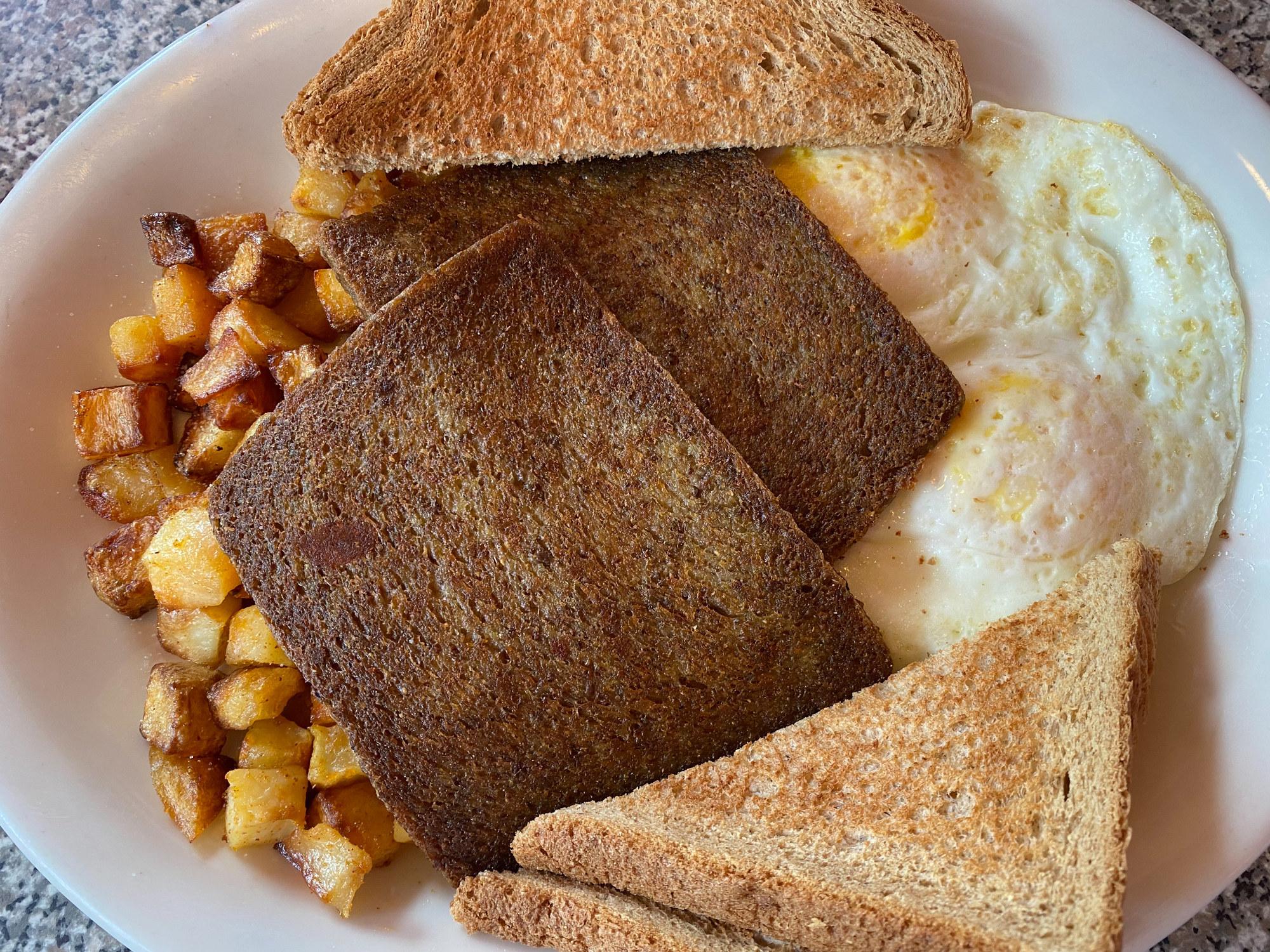Scrapple, eggs, potatoes, and toast.