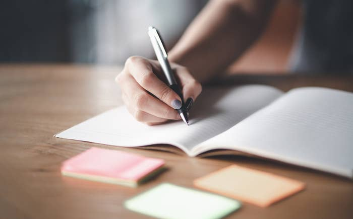 A stock image of someone writing in a journal