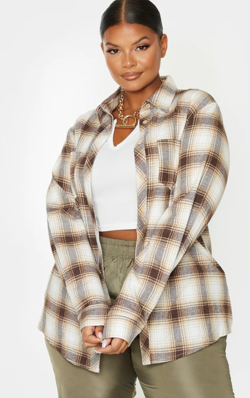 model wearing the flannel oversized shirt over a white shirt and green pants