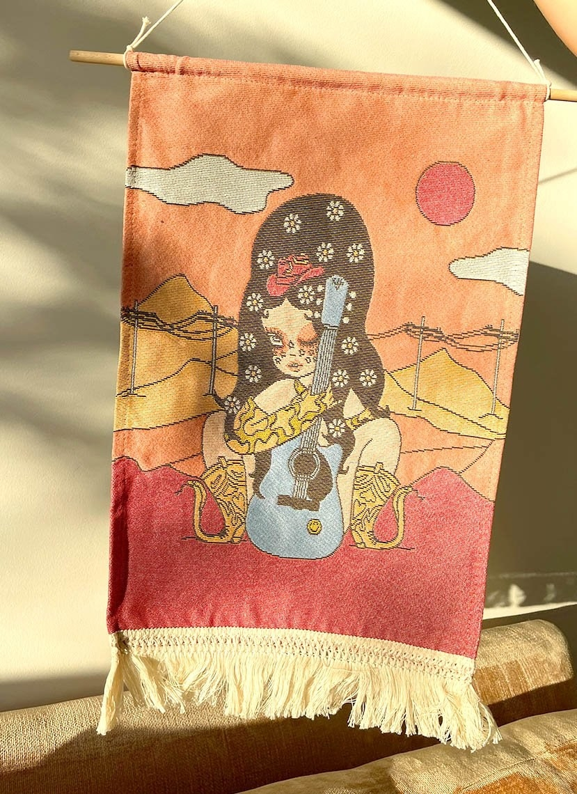a tapestry with an illustration of a cowgirl holding a guitar