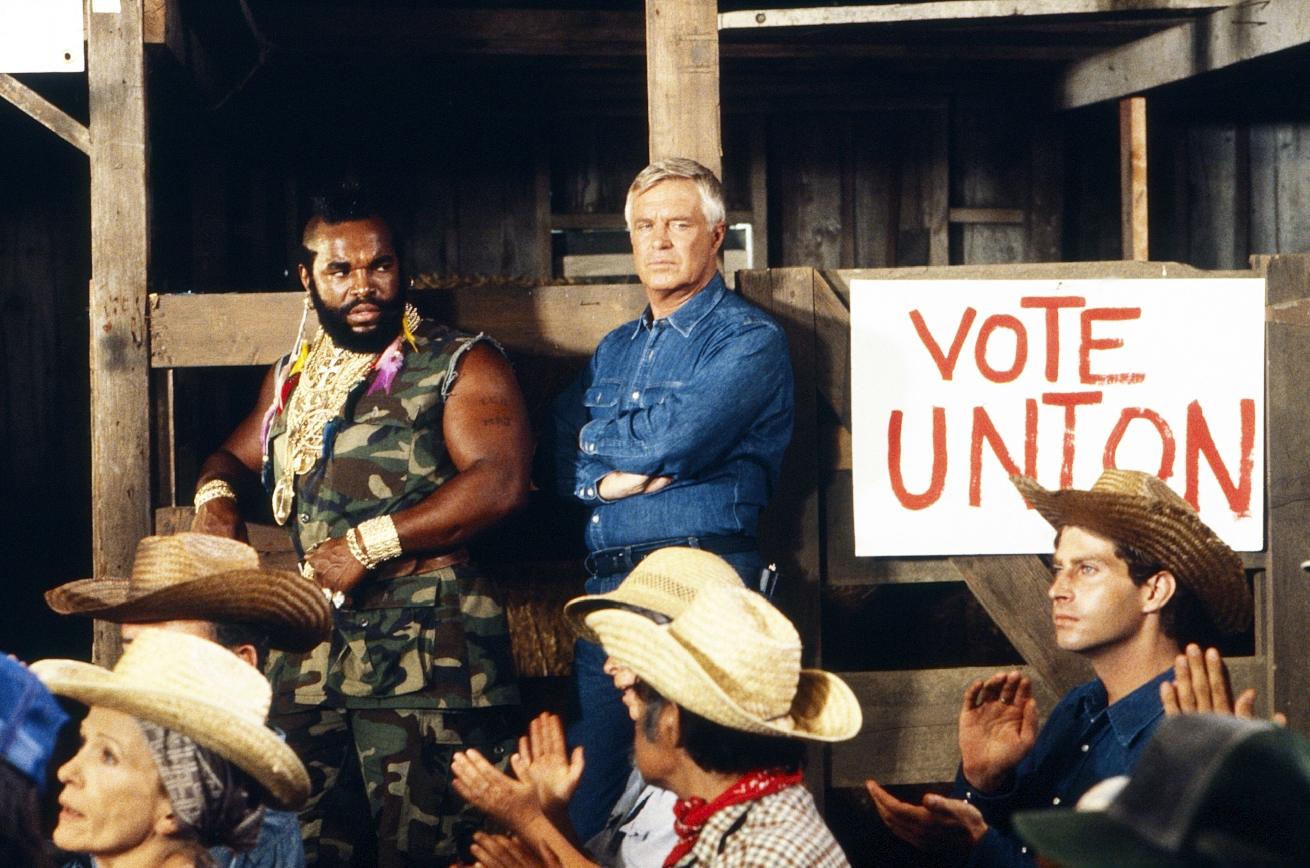 Mr. T and George Peppard eye a room full of cowboys