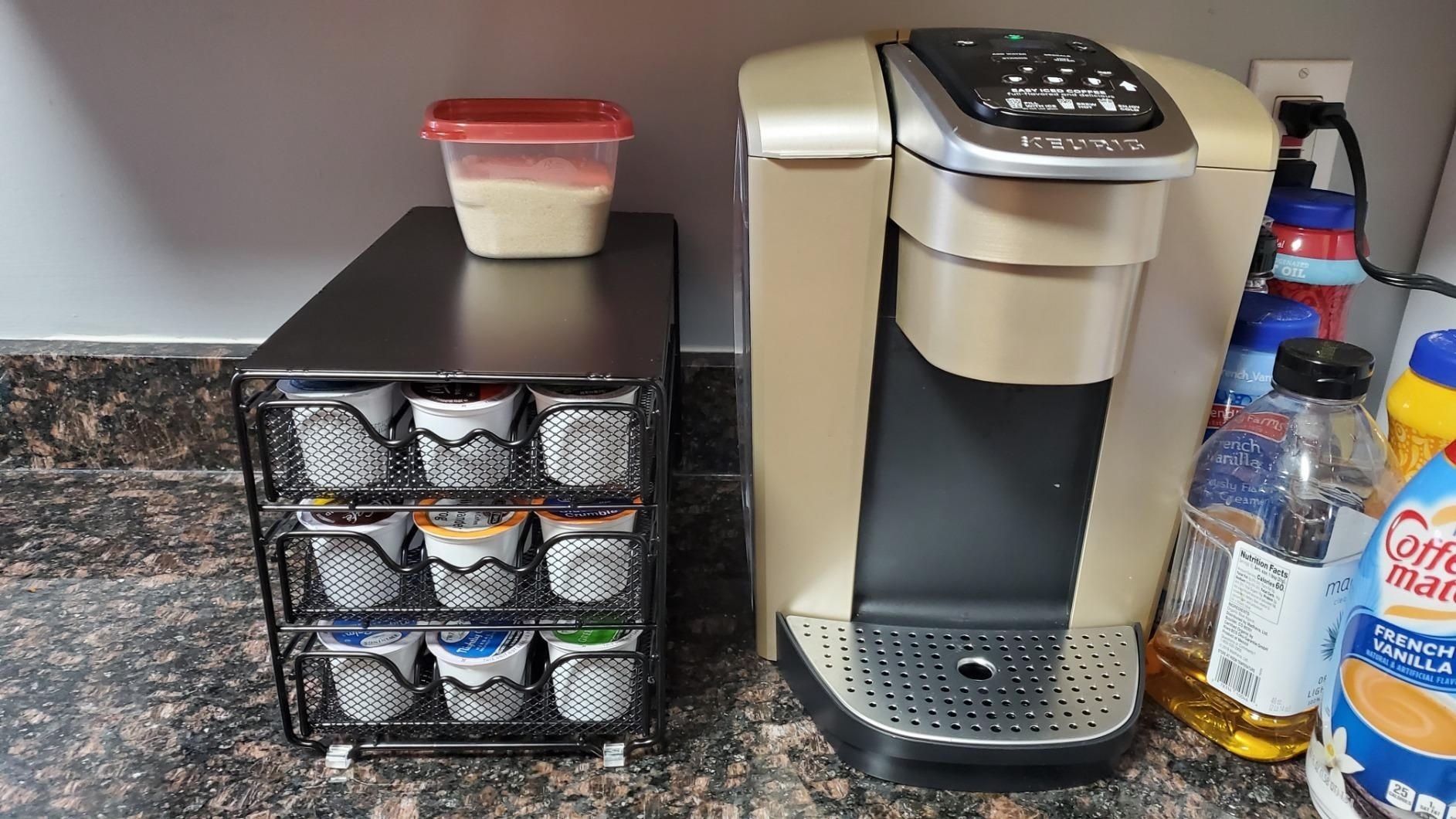 reviewer image of the K-cup organizer next to a keurig machine on a kitchen counter