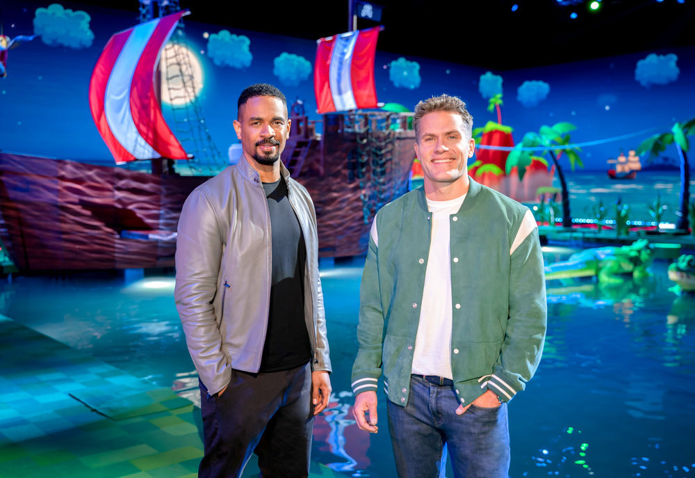 Hosts Damon Wayans Jr. and Kyle Brandt stand in front of the Frogger course