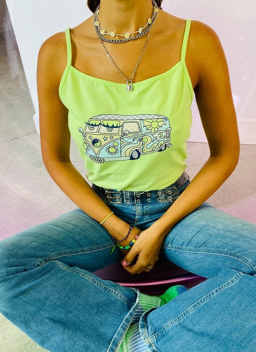 a model in a neon green tank with a groovy '70s-styled van on it