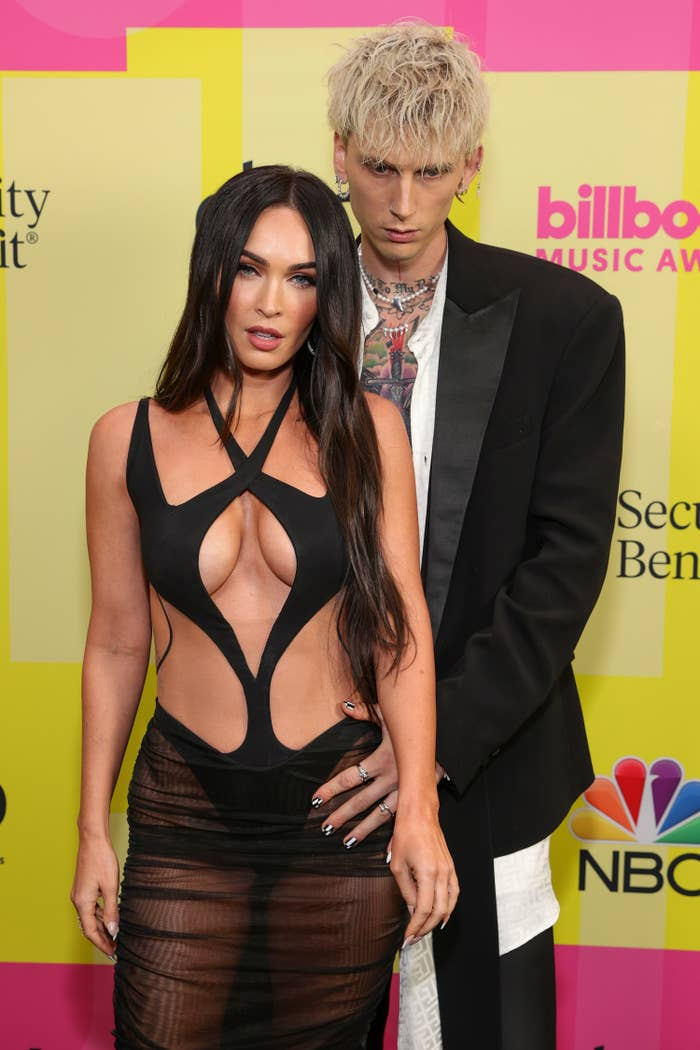 MGK holding onto Megan's waist as they pose for photos on a red carpet