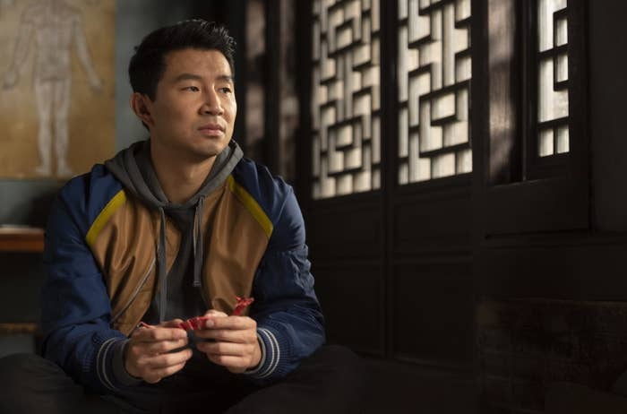 Shang-Chi, wearing a hoodie and a jacket, sitting in a scene from the film