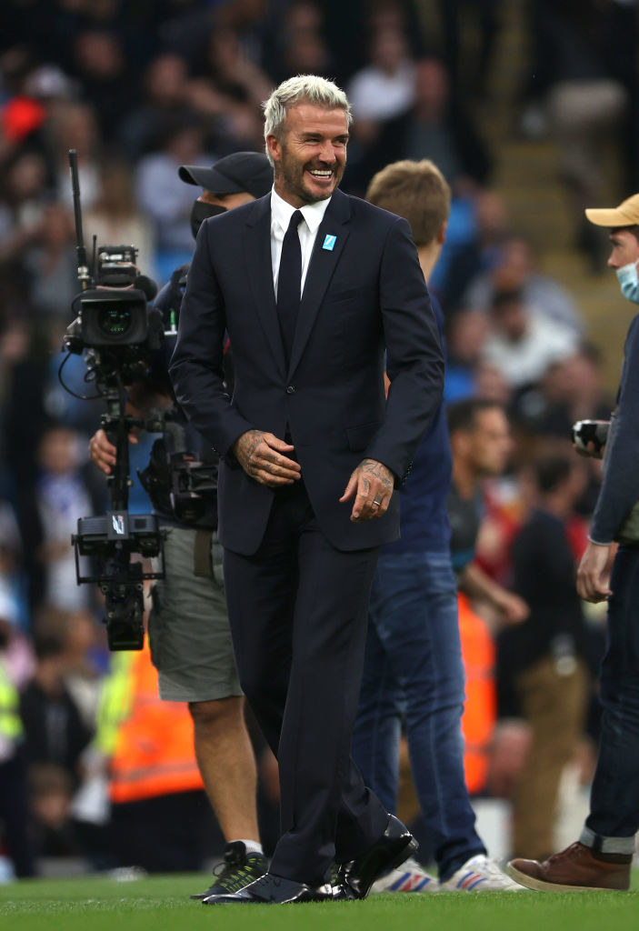 Smiling at a soccer game, but wearing a suit, not a uniform