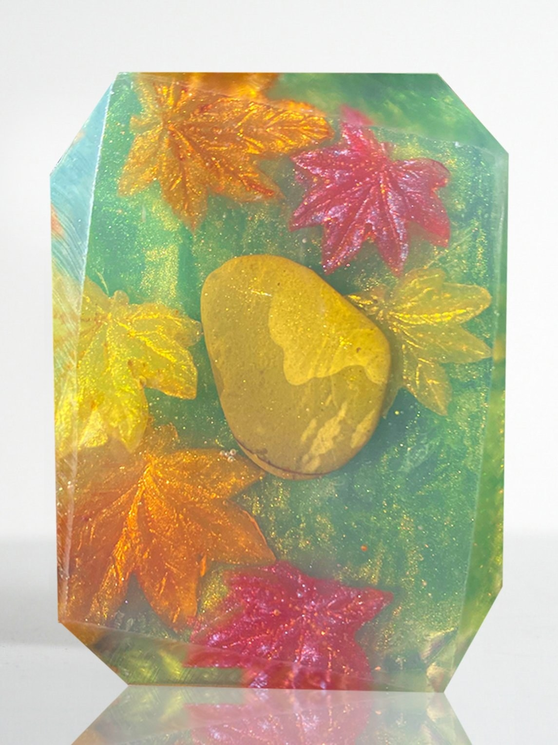 a bar of soap with leaves in it and a crystal stone