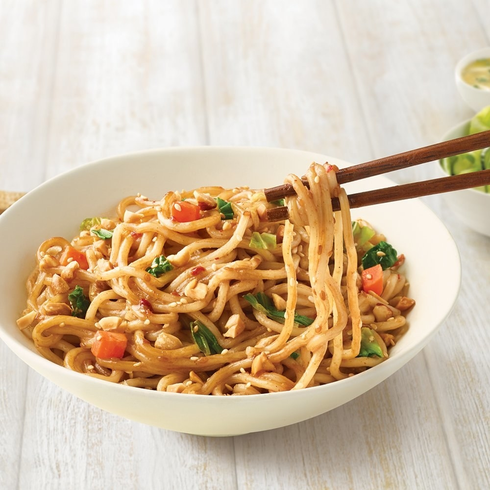the noodles in a bowl with a pair of chopsticks