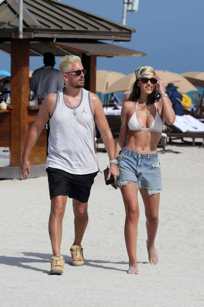 Scott and Amelia walking hand-in-hand on the beach