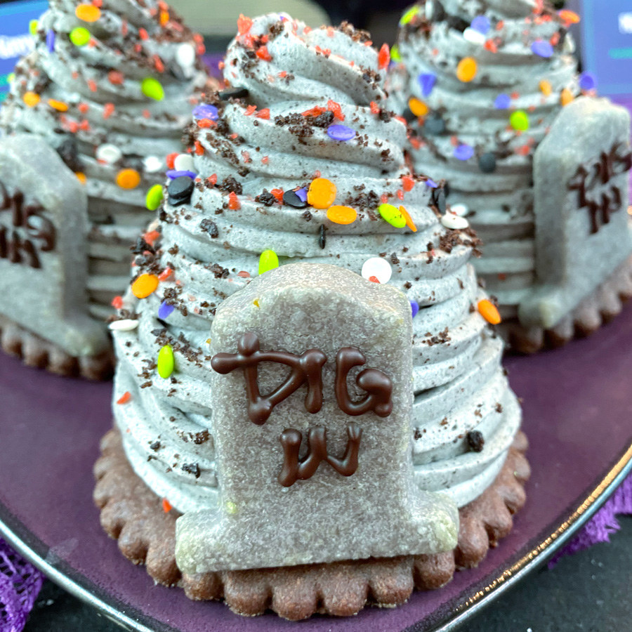 """A swirl of grey mousse on top of a round cookie, and an cookie on top of it all in the shape of a tombstone that says """"dig in"""""""