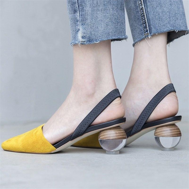 model wearing pointed-toe shoes with rounded half-clear heel