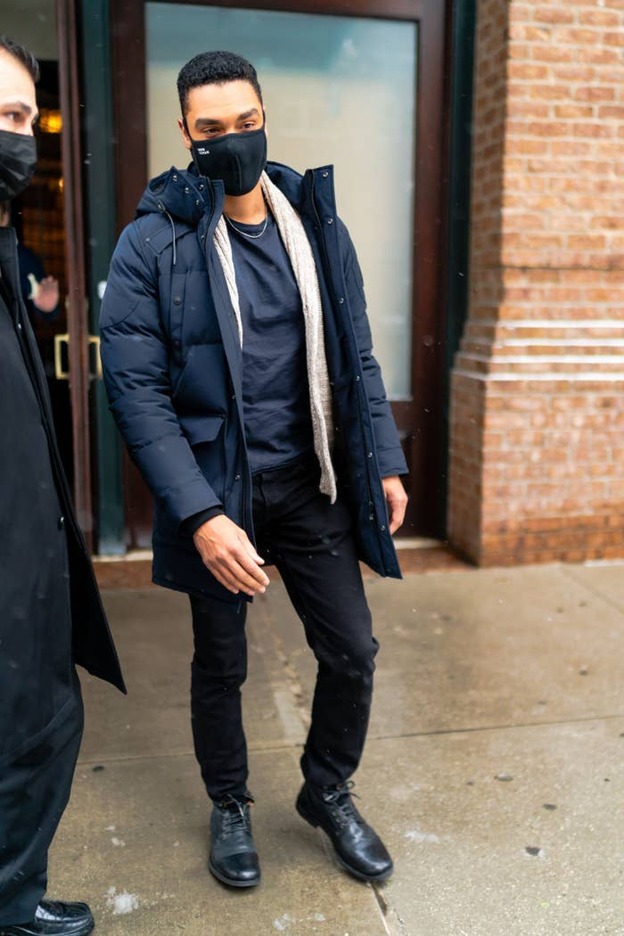 Regé-Jean Page walking out of a building with a face mask and a puffer jacket