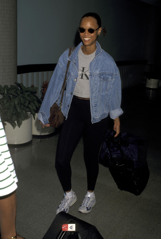 Tyra Banks wearing black pants and a denim jacket at the airport
