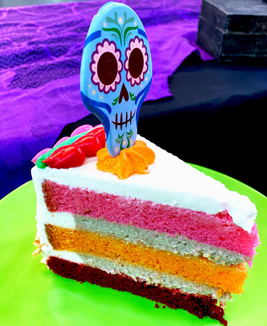 A three layered cake with 3 layers in pink, orange, and red, and a skull shaped decoration on top that has a cute face with flower eyes that's smiling